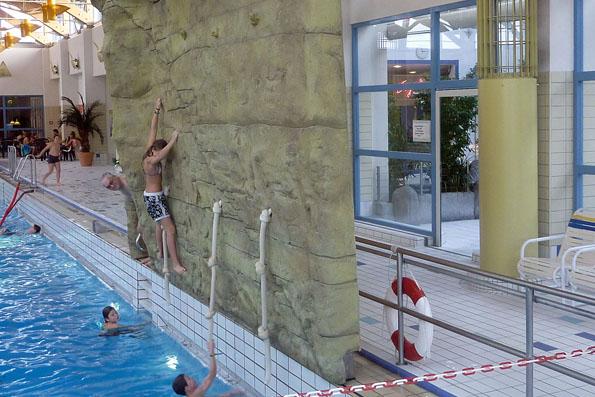 """In der Altmühltherme lockt unter anderem das """"Aquabouldering"""" - eine Kletterwand, von der aus man sich direkt ins Becken fallen lassen kann. (Foto: djd)"""