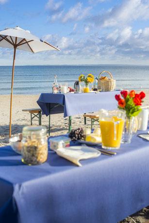 An der schleswig-holsteinischen Ostseeküste warten am 6. Juli gedeckte Frühstückstische auf die Gäste. (Foto: djd)