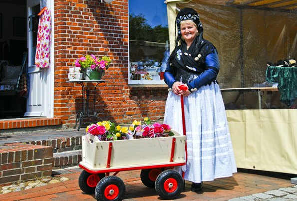 In traditionellen Tracht präsentieren die Bewohnerinnen von Pellworm die Blütenpracht der Insel. (Foto: Nordsee Tourismus)
