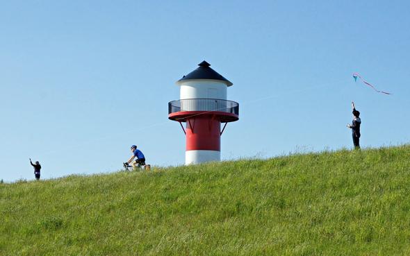 Radfahrer auf dem Elberadweg: Leuchttürme sind die Wegweiser der maritim geprägten Urlaubsregion Altes Land am Elbstrom. (Foto: Martin Elsen)