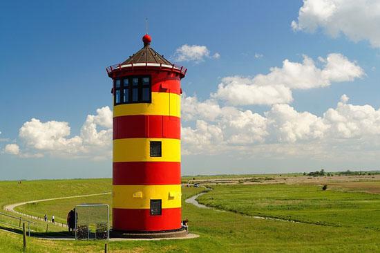 Der gelbrot geringelte Pilsumer Leuchtturm grüßt die Radler auf dem Nordsee-Radweg. (Foto: djd)