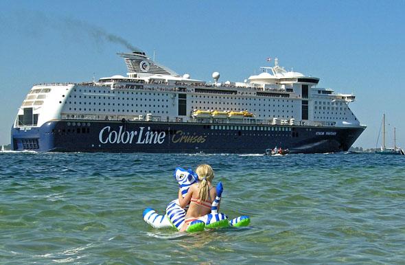 """Badespaß mit Blick auf die """"großen Pötte"""". Auf der Kieler Förde tummeln sich Urlaubsgäste ebenso wie die großen Skandinavien-Fähren oder Kreuzfahrt-Riesen. (Foto: djd)"""