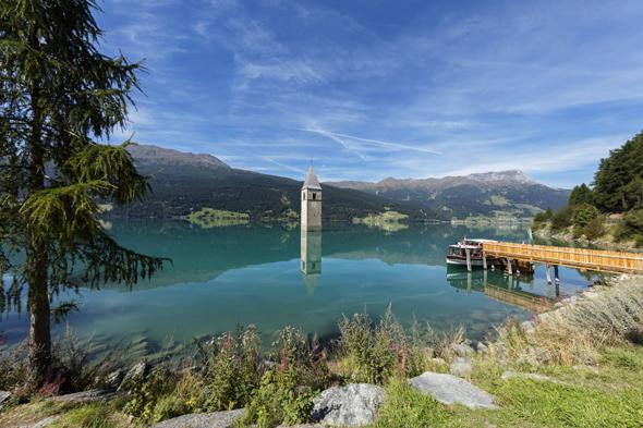 Mit sechs Kilometern Länge und 120 Millionen Kubikmeter Stauvolumen ist der Reschensee Südtirols größter Wasserspeicher. Bildnachweis: Vinschgau Marketing/Frieder Blickle