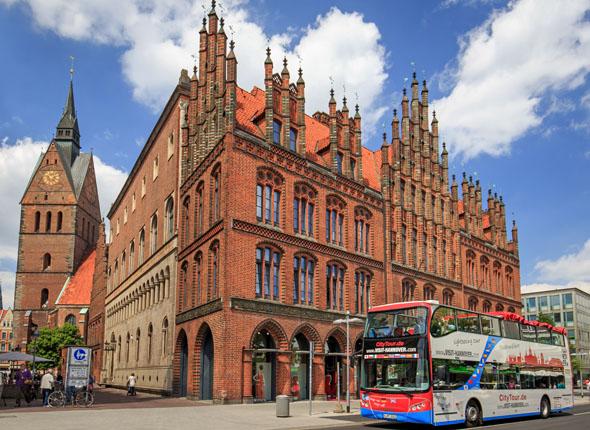 Der Doppeldecker-Bus nimmt Rollstuhlfahrer mit auf die Stadtrundfahrt, die auch an Hannovers Altem Rathaus und der Marktkirche entlang führt. (Foto djd)