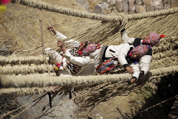 Die Inkas hängen förmlich in den Seilen, wenn sie gemäß jahrhundertealter Tradition die Hängebrücke Q'eswachaka anbringen.