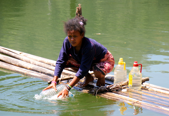 Eine Orang Asli Frau in Kampung Chuweh hoöt Wasser mit Hilfe ihres Bambus-Flosses. (Foto Karsten-Thilo Raab)