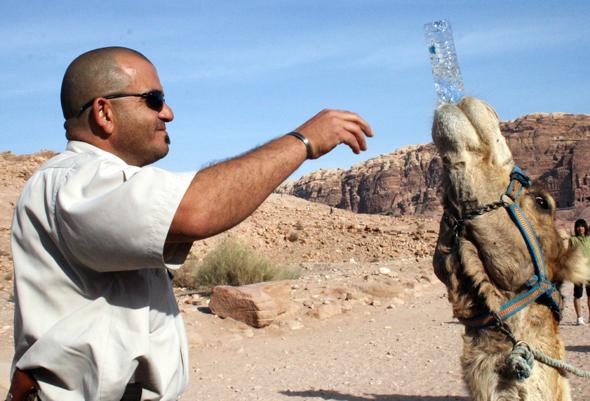 Raef teilt sein Wasser mit einem durstigen Dromedar. - Foto Karsten-Thilo Raab
